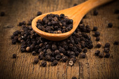 Black pepper on wooden spoon. And wood background Stock Images