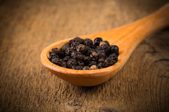 Black pepper on wooden spoon. And wood background Royalty Free Stock Photo