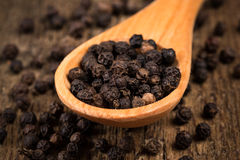 Black pepper on wooden spoon. And wood background Royalty Free Stock Image