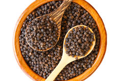 Black pepper on wooden spoon with wooden plate isolated Stock Photography