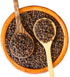 Black pepper on wooden spoon with wooden plate isolated Royalty Free Stock Photo