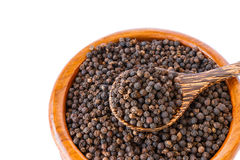 Black pepper on wooden spoon with wooden plate isolated Royalty Free Stock Photos