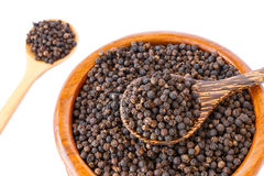 Black pepper on wooden spoon with wooden plate isolated Royalty Free Stock Image