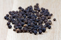 Black pepper on wooden surface Royalty Free Stock Photos