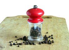Black peppercorn and manual mill with red cap on wooden kitchen board isolated on white close up Royalty Free Stock Photos