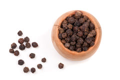 Black peppercorn in a wooden bowl isolated on white background. Top view Stock Photos