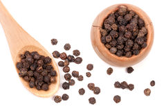 Black peppercorn in a wooden bowl and spoon isolated on white background. Top view Stock Photography