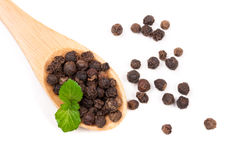 Black peppercorn in a wooden spoon isolated on white background. Top view Royalty Free Stock Photo