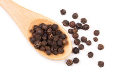Black peppercorn in a wooden spoon isolated on white background. Top view Royalty Free Stock Image