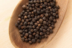 Black peppercorn on a wooden spoon Stock Photo