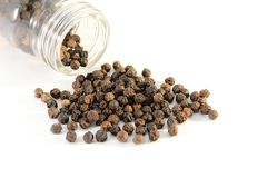 Black peppercorns. Poured from a glass jar.Isolated on white background royalty free stock photography