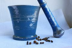 Black peppercorns and allspice in ancient metal mortar with pestle on linen background royalty free stock photography