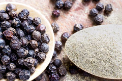 Black peppercorns and black pepper powder on wooden spoon. Royalty Free Stock Images