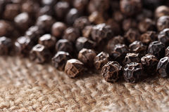Black peppercorns on a hessian background Royalty Free Stock Photography