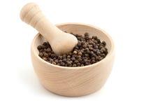 Black peppercorns in mortar Stock Images