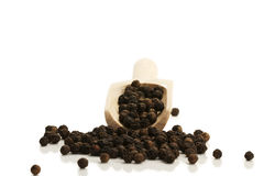Black peppercorns from a small wooden shovel front Stock Photos