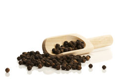 Black peppercorns with a small wooden shovel side Royalty Free Stock Photography