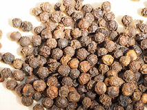 Black peppercorns on a wooden board. Macro image of a pile of black peppercorns Royalty Free Stock Photos