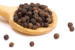Black Peppercorns on a wooden spoon Stock Image