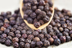 Black peppercorns on wooden spoon. Royalty Free Stock Images