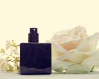 Black perfume bottle and flower Stock Photo