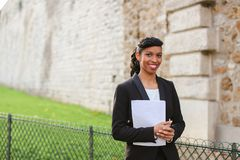Mix blood secretary talking with smartphone and reading papers. Black person secretary talking with boss by mobile phone, reading papers and strolling. Pretty Royalty Free Stock Photography
