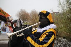 Black Pete, the helper of dutch traditional celebration of Sinterklaas making music. This became big discussion about the black face which could be rascism stock photos