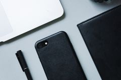 Black phone, black notebook and black pen with silver laptop on table top, close-up, top view, office, work, flatlay. Working, workspace, office stock image