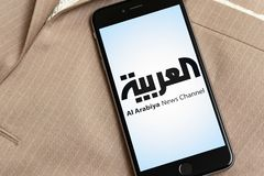Black phone with logo of news media Al Arabiya on the screen. stock photography