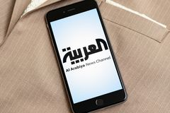 Black phone with logo of news media Al Arabiya on the screen. stock image