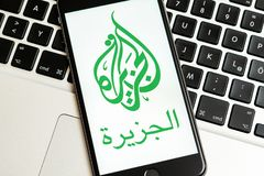 Black phone with logo of news media Al Jazeera on the screen. stock image