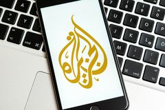 Black phone with logo of news media Al Jazeera on the screen. stock photo