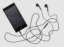 Phone and music. Black phone with ultramodern earphones on a white background Royalty Free Stock Images