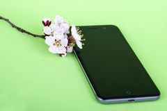 Black phone with white flower on green background. Mobile phone and sakura stock photo