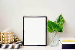 Black photo frame, green plant in a crystal vase, gift boxes and a pile of books arranged against empty grey wall. Frame mock-up. Black photo frame, green plant royalty free stock image