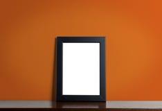 Black photo frame on orange background. stock images