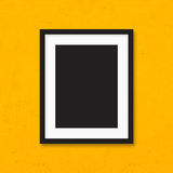 Black photo frame on yellow wall background. Royalty Free Stock Photography