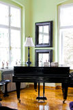 Black piano. In room with big windows stock photos