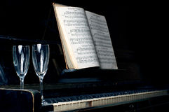 Black piano. Standing in the darkness with notes and two glasses on it Royalty Free Stock Images