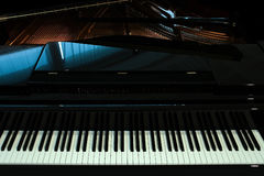 Black piano closeup. Closeup view of one beautiful big shiny black open piano forte with white key board standing in studio with no people, horizontal picture Stock Photo