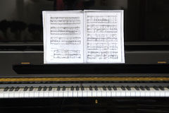 Black piano with sheet music. Situated in a room royalty free stock photos