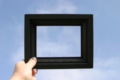 Black picture frame is held against a blue sky by a real human hand. A black picture frame is held against a blue sky by a real human hand stock photography