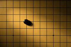 Black piece GO and board. A black piece GO and board Royalty Free Stock Photo