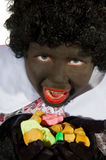 Black Piet is eating pepernoten Royalty Free Stock Photo