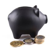 Black piggy bank with euro coins isolated Royalty Free Stock Image