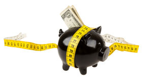Black piggy bank with measuring tape Royalty Free Stock Image