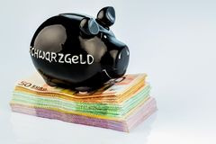Black piggy bank on money Stock Image