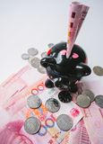 Black piggy bank standing on Chinese 100 rmb banknotes and coins royalty free stock photos