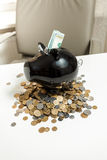 Black piggy bank standing on pile of coins on white table Stock Photo