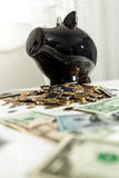 Black piggy bank standing on pile of money Stock Image